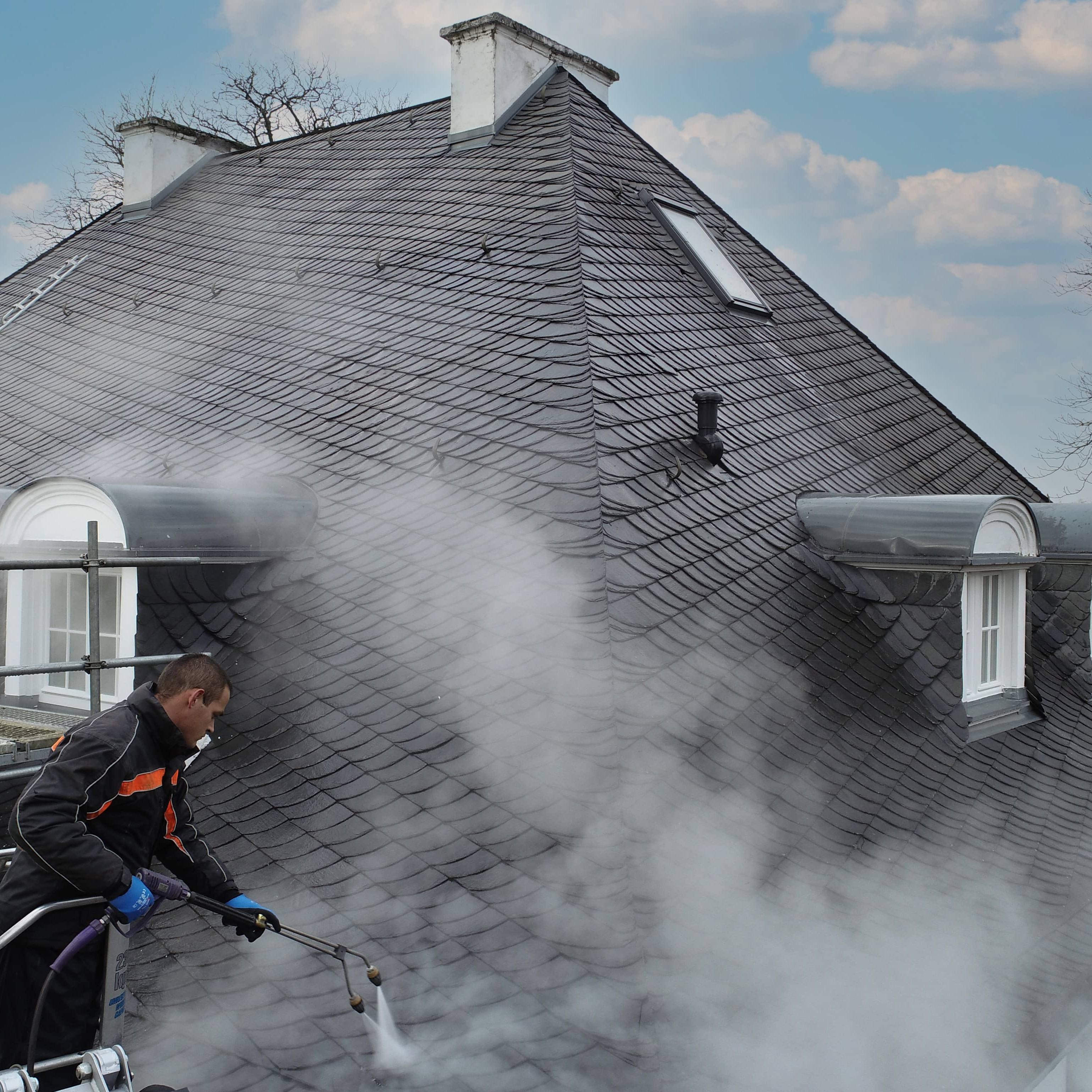 Das Bild zeigt zwei Dacharbeiter. Der eine Arbeiter im Vordergrund reinigt das Schieferdach mit einer speziellen Reinigungslanze.