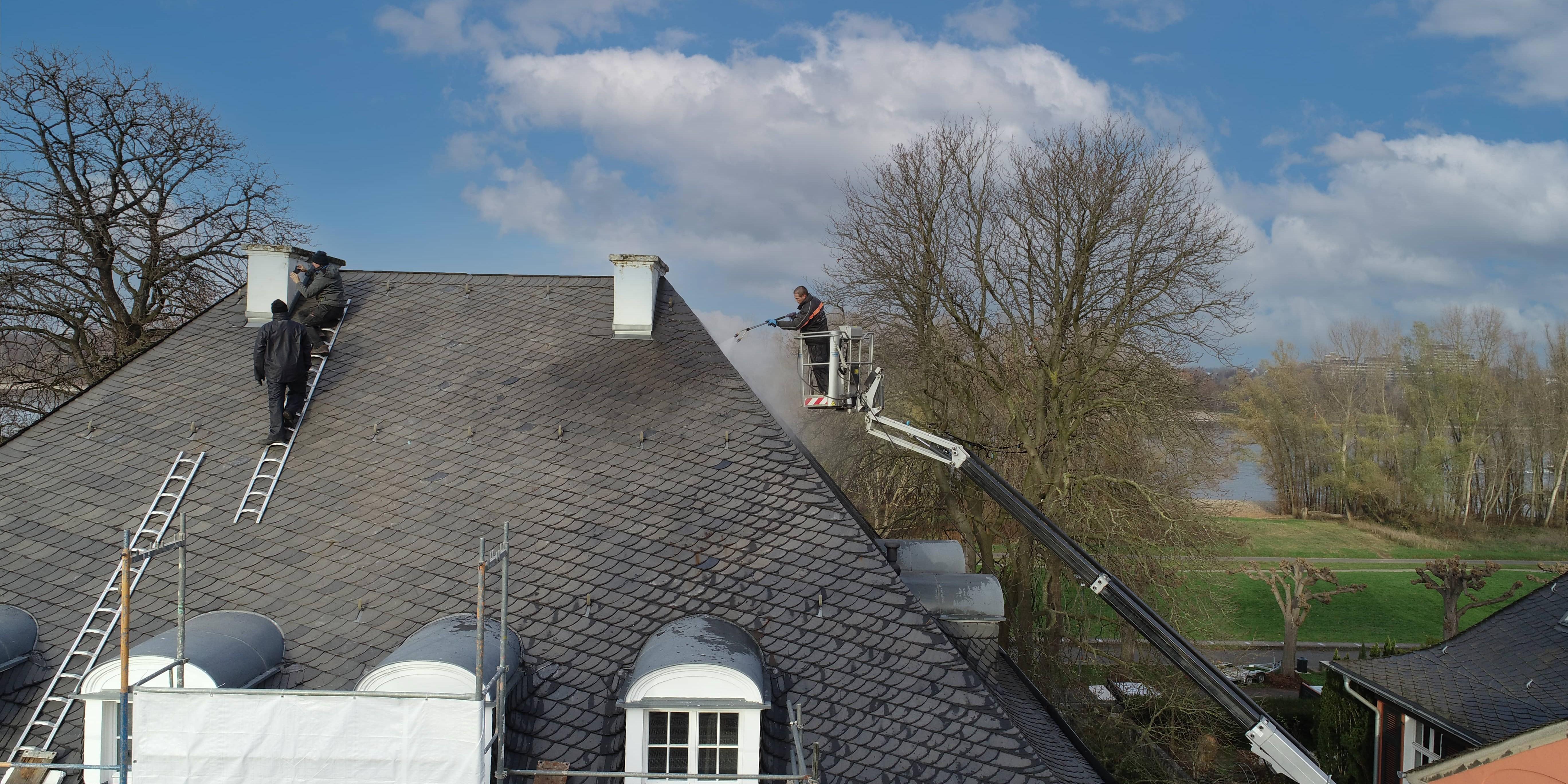 Das Bild zeigt drei Dacharbeiter, die ein Schieferdach reinigen.