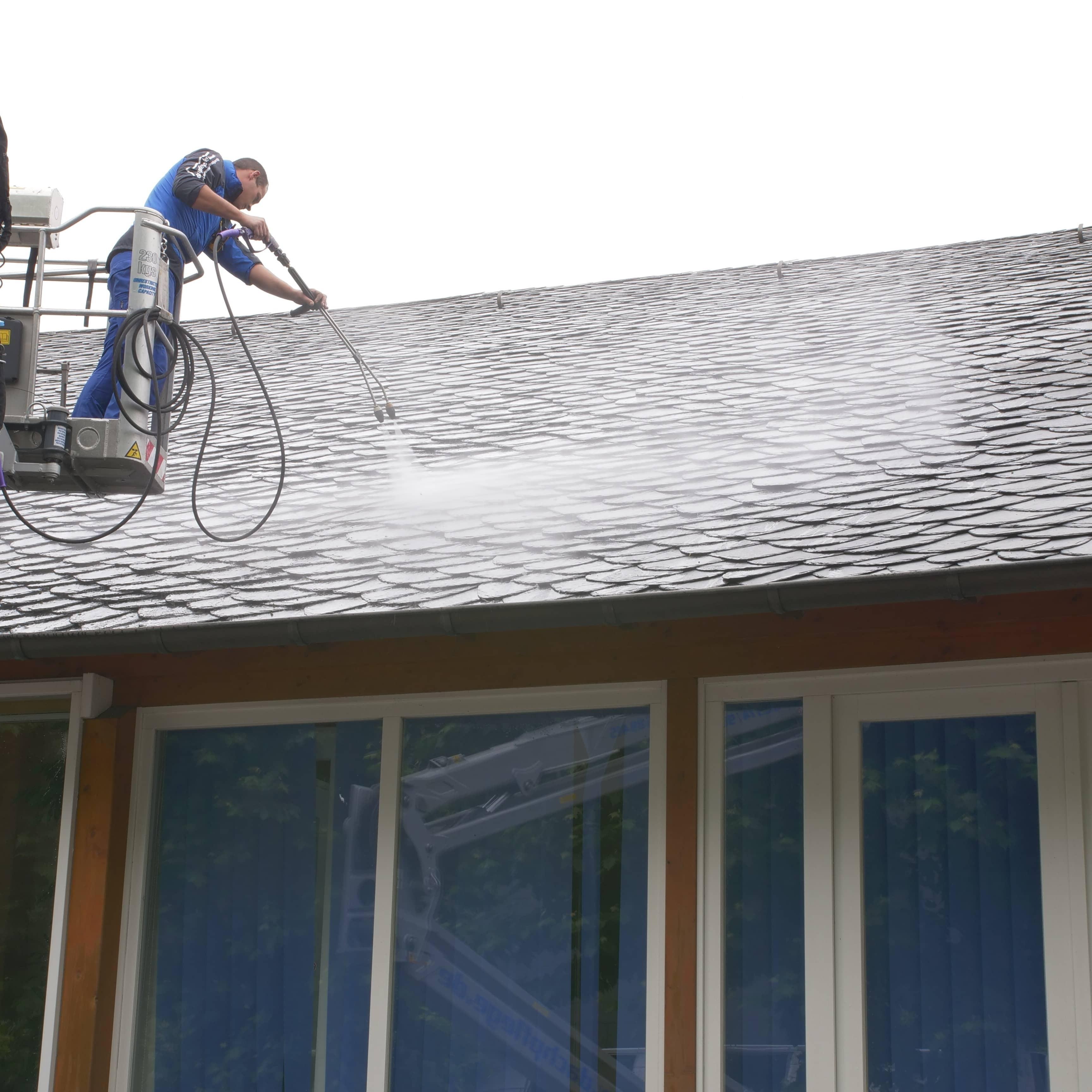 Das Bild zeigt einen Dachreiniger des Teams, der das Schieferdach reinigt. Dafür nutzt er eine spezielle Lanze.